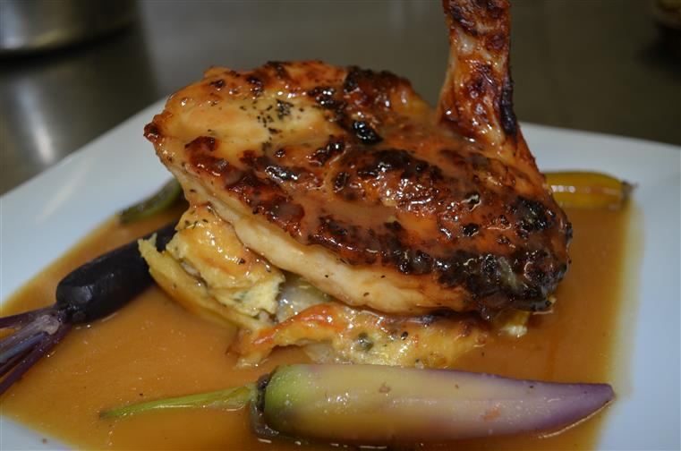 Grilled chicken served with sauce and vegetables