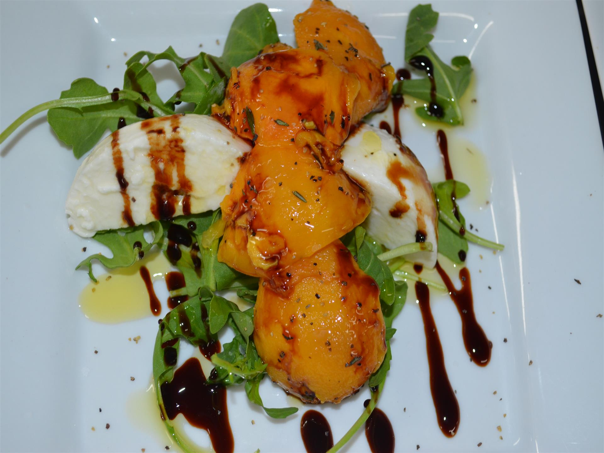 Braised peach served with fresh greens, cream cheese and balsamico