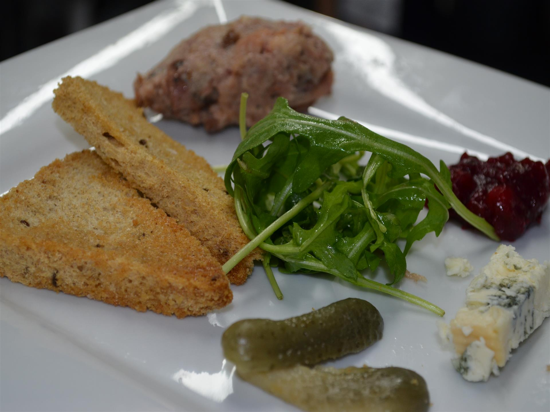 Fried dish served with arugula, blue cheese and pickles