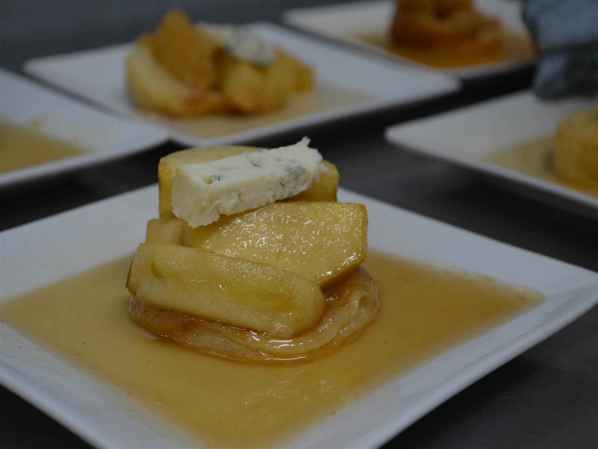 Pancake topped with apples and blue cheese, served with maple syrup
