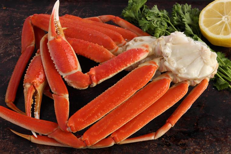 Crab legs and garnish on stone table