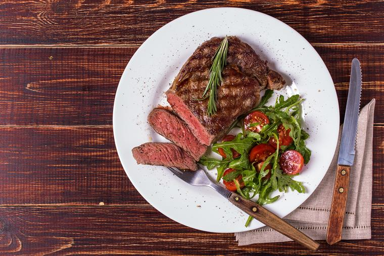 Sliced steak with greens and tomatoes on white plate on rustic wood table