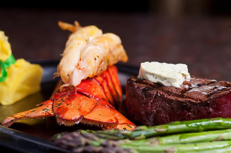 Lobster, steak, asparagus on black dish