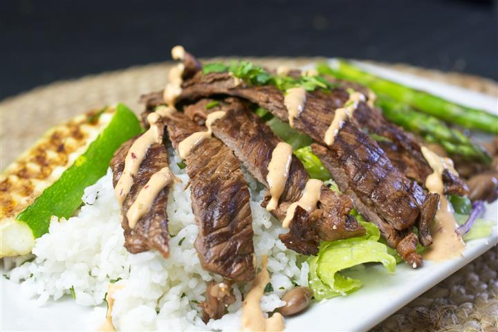 Grilled Steak topped with sauce and served with rice
