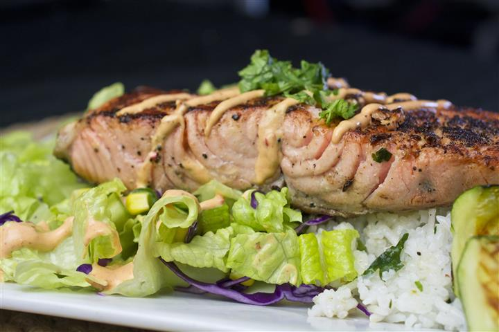 Grilled salmon served with rice, topped with sauce