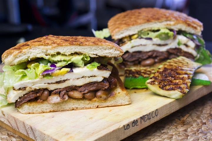 Two tasted sandwiches with chicken, black beans, lettuce, & sauce