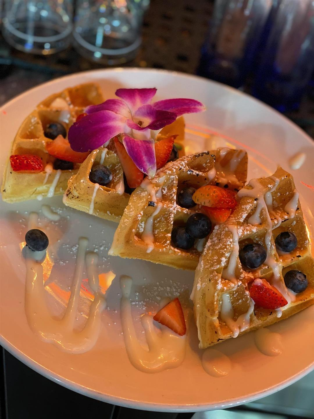 waffles with blueberries, strawberries, and a drizzle of icing with a flower on top