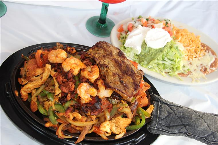 fajita with steak, shrimp and vegetables on a skillet with a side of rice, beans, pico de gallo, sour cream and guacamole