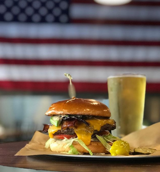 @GooseLoonies - Cheeseburger on bar next to beer. In front of an American Flag