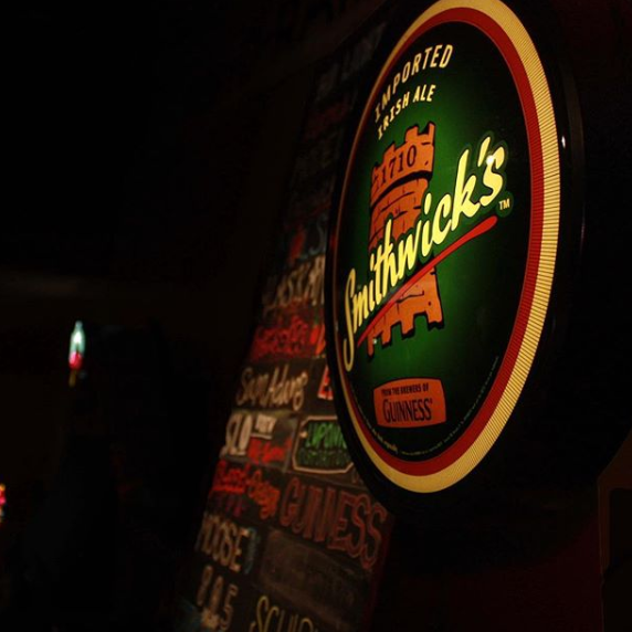 Neon Smithwick's Beer Logo in front of Beer List chalkboard