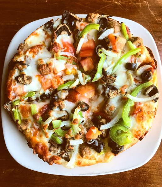 Pizza topped with Peppers, Onions, and Mushrooms
