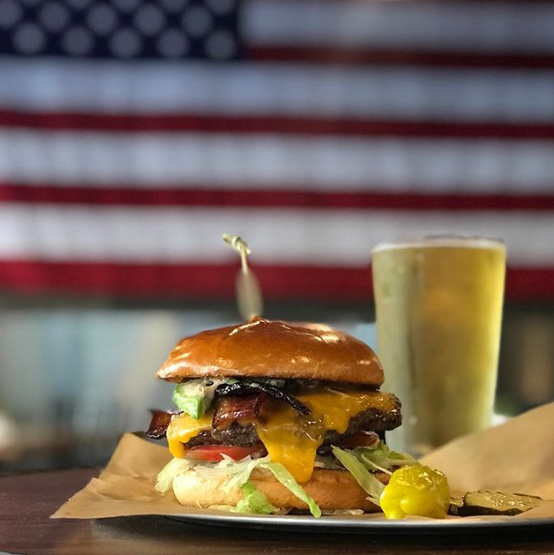 Burger on Bar next to Beer in front of American Flag