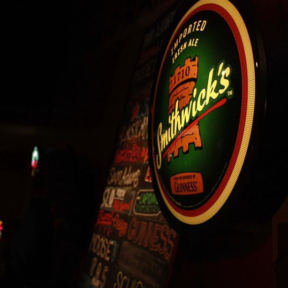 Smithwick's neon sign in front of chalkboard beer list