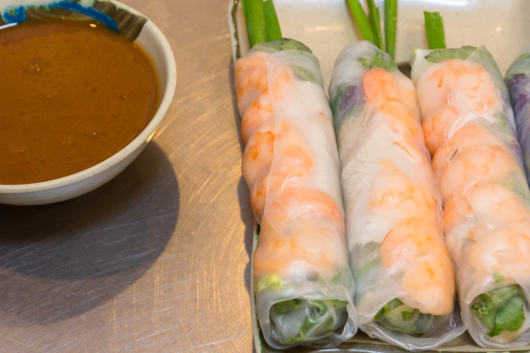three spring rolls on a plate with scallions and a small bowl of dipping sauce
