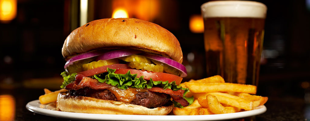 cheeseburger with bacon, lettuce, pickles, onions and tomatoes. french fries and glass of beer on the side.