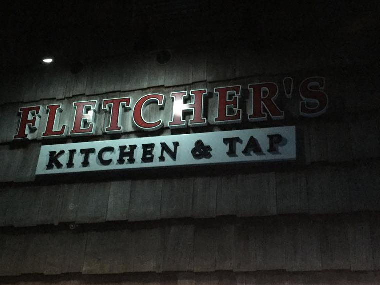 outside sign that reads fletcher's kitchen and tap