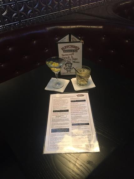 a menu and two alcoholic drinks on a table