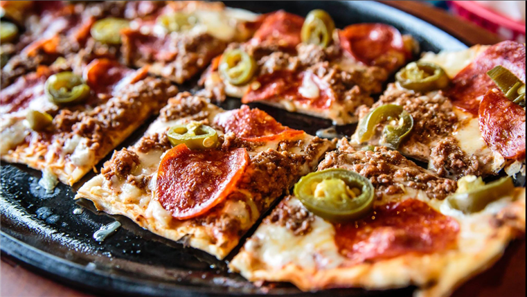 Square pieces of mexican pizza topped with jalapenos and chorizo