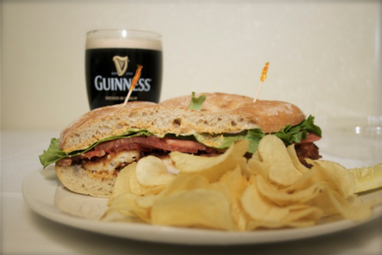 sub sandwich with potato chips on a plate. glass of beer in the background.