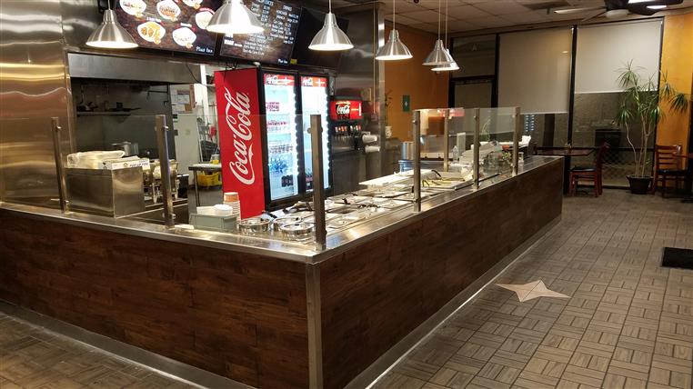 interior counter area with a digital menu hanging behind