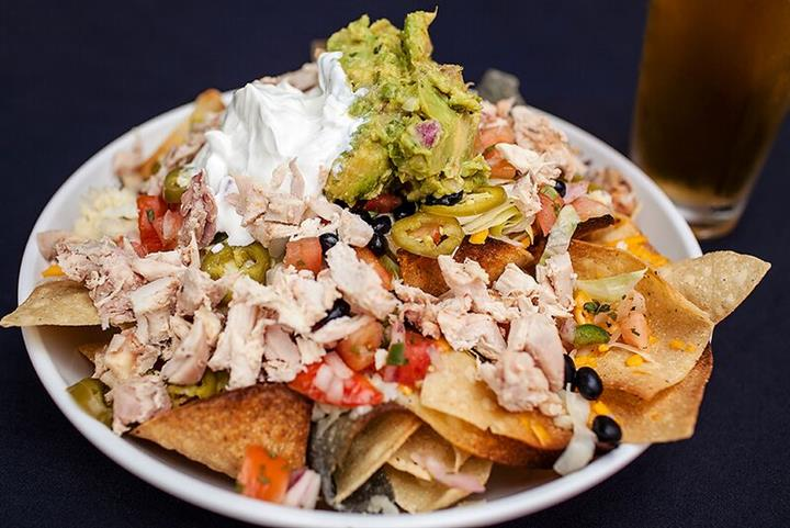 Nachos. Tri-corn tortilla chips topped with cheese sauce and melted cheeses, fresh salsa, lettuce, black beans, jalapenos and smoked chicken.