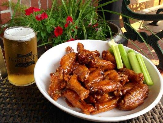 Plate of chicken wings and celery with glass of beer.