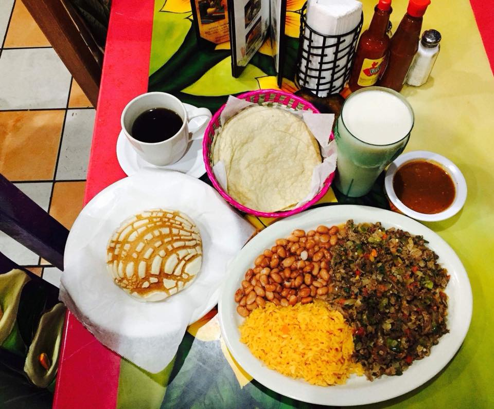 Beans, rice, greens on dish next to soft tortillas in basket, coffee, milk, dipping sauce