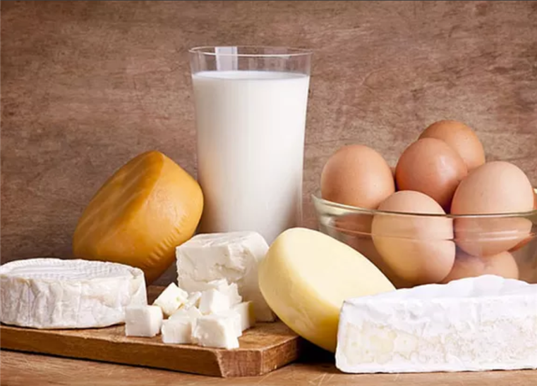 glass of milk, eggs and various cheese