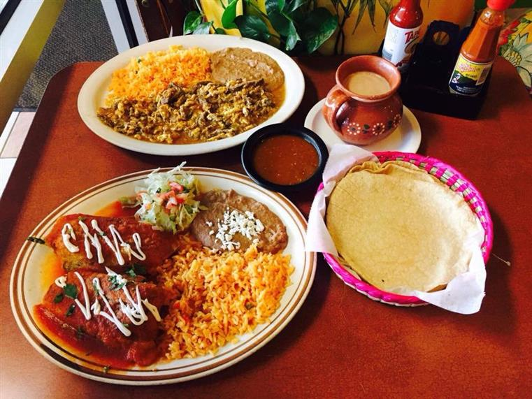 Plates of enchiladas, rice, refried beans, soft tortilla shells, dipping sauce, cup of coffee.