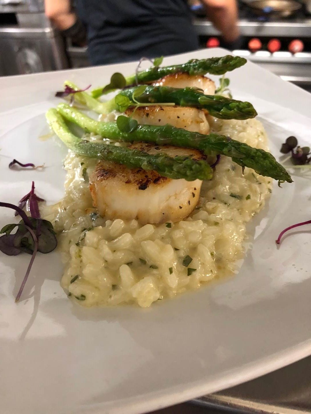 Scallops over risotto with asparagus