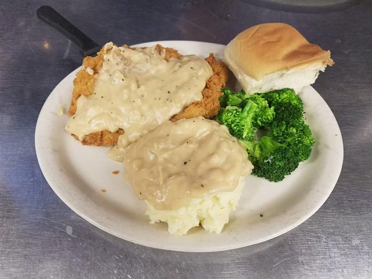 country fried steak smothered in gravy with mashed potatoes, broccoli and roll