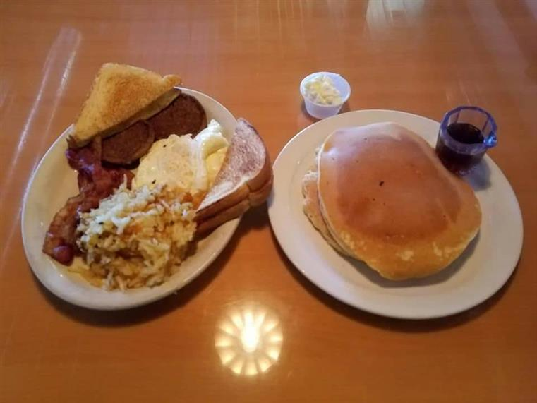 pancakes on one plate. eggs, hashbrowns, bacon and toast on another plate.