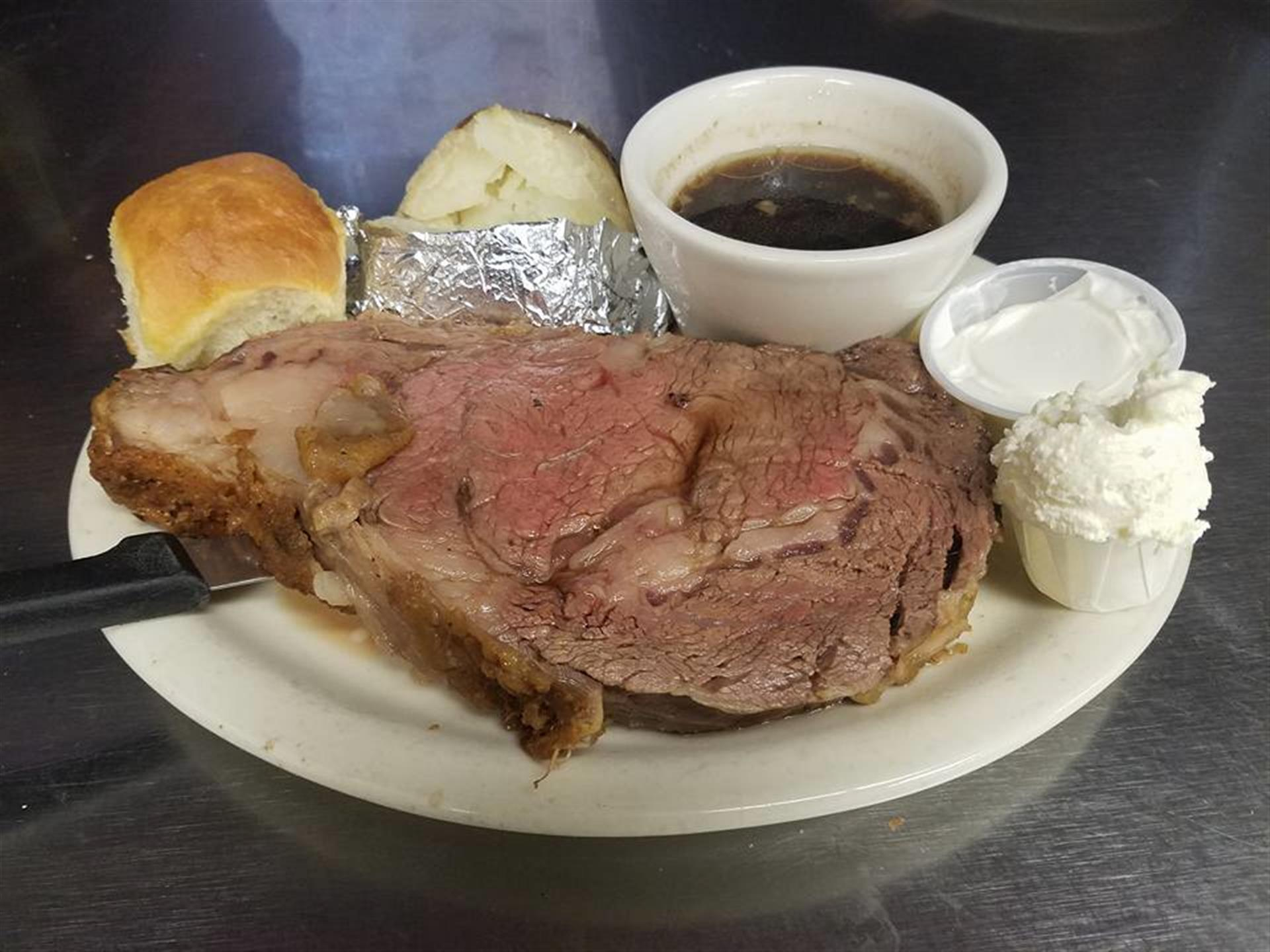 roast beef with baked potato in tin foil and roll