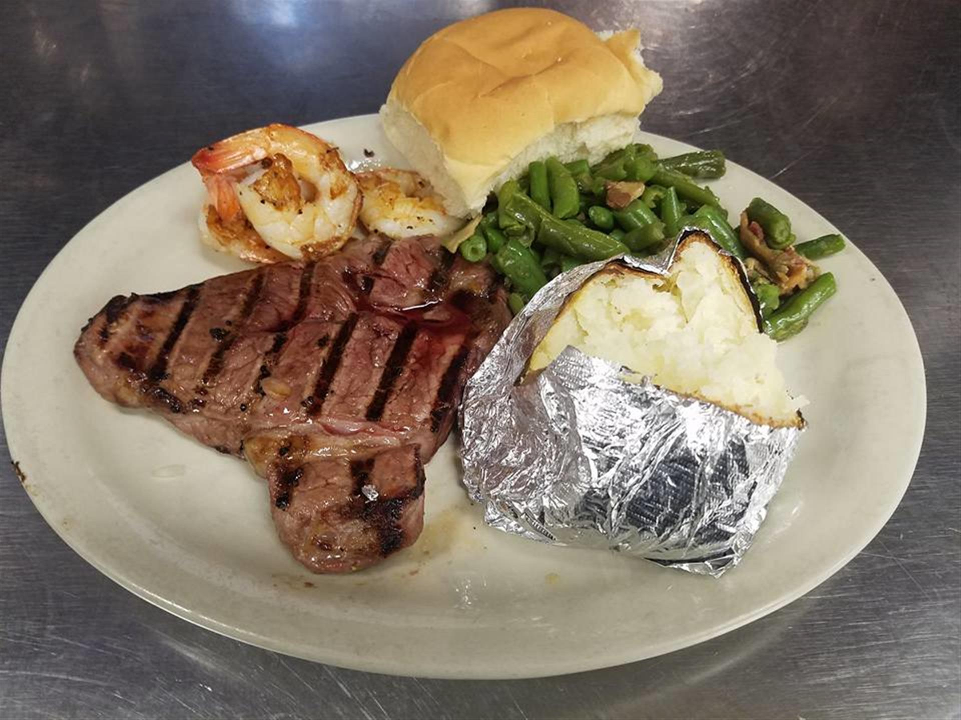 steak with green beans, baked potato in tin foil, shrimp, and roll