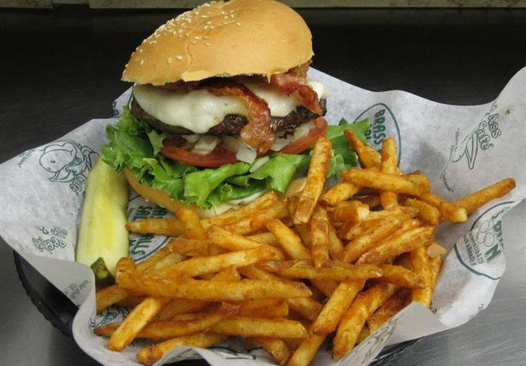 highly-stacked burger with lettuce, tomato, cheese, bacon and bun. Side of fries and pickle.