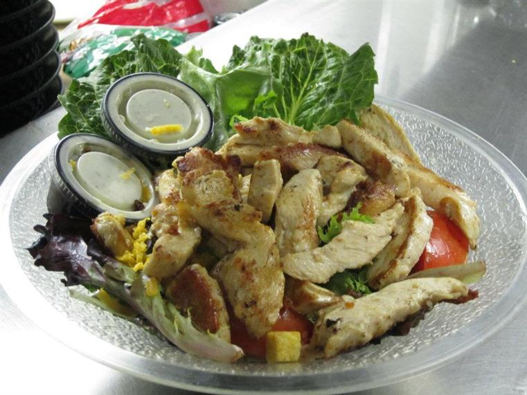 Salad with chicken, croutons, tomatoes and dressing on the side in clear dish.
