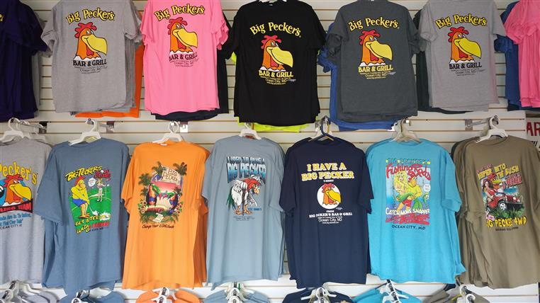 Rows of big peckers tee shirts on wall