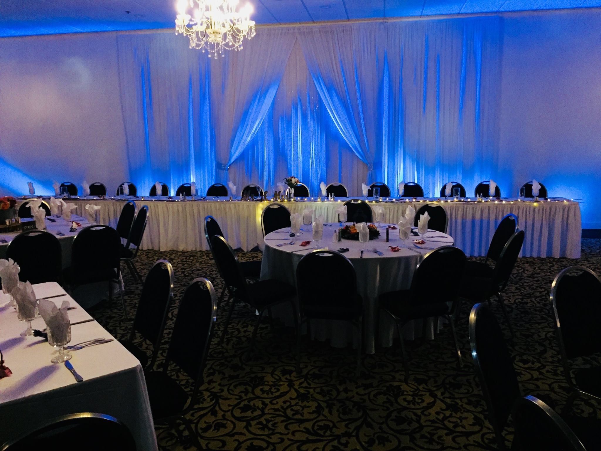 large event room with many tables covered in white cloths with silverware and wine glasses