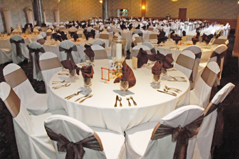 large event room with many tables covered in white cloths with silverware, wine glasses and tall candle in middle of the table