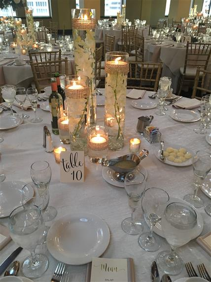 large table covered in a white cloth with silverware and plates and candles lit in the middle