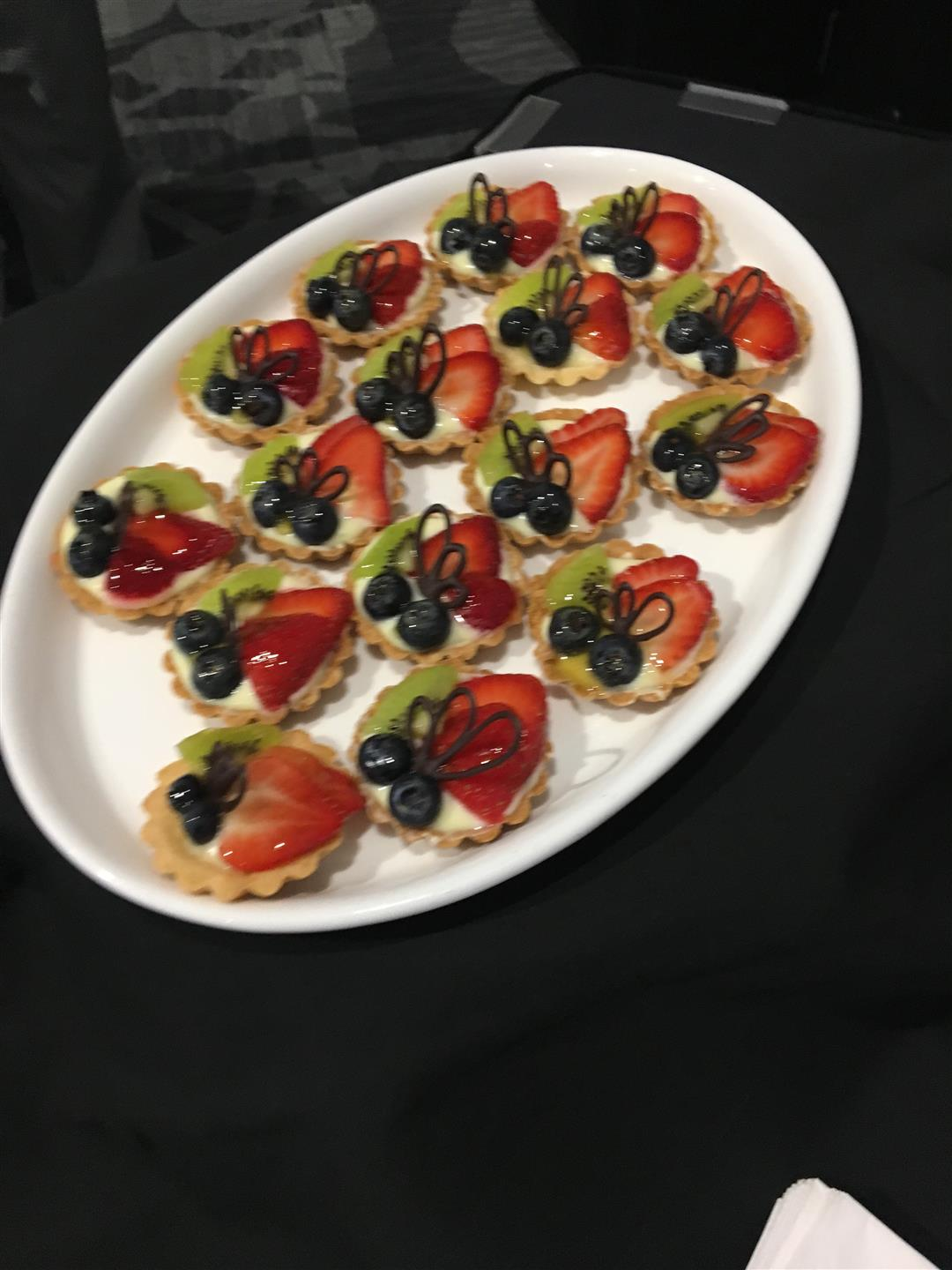 Fruit tart with strawberries, kiwi, blueberries and custard on a platter