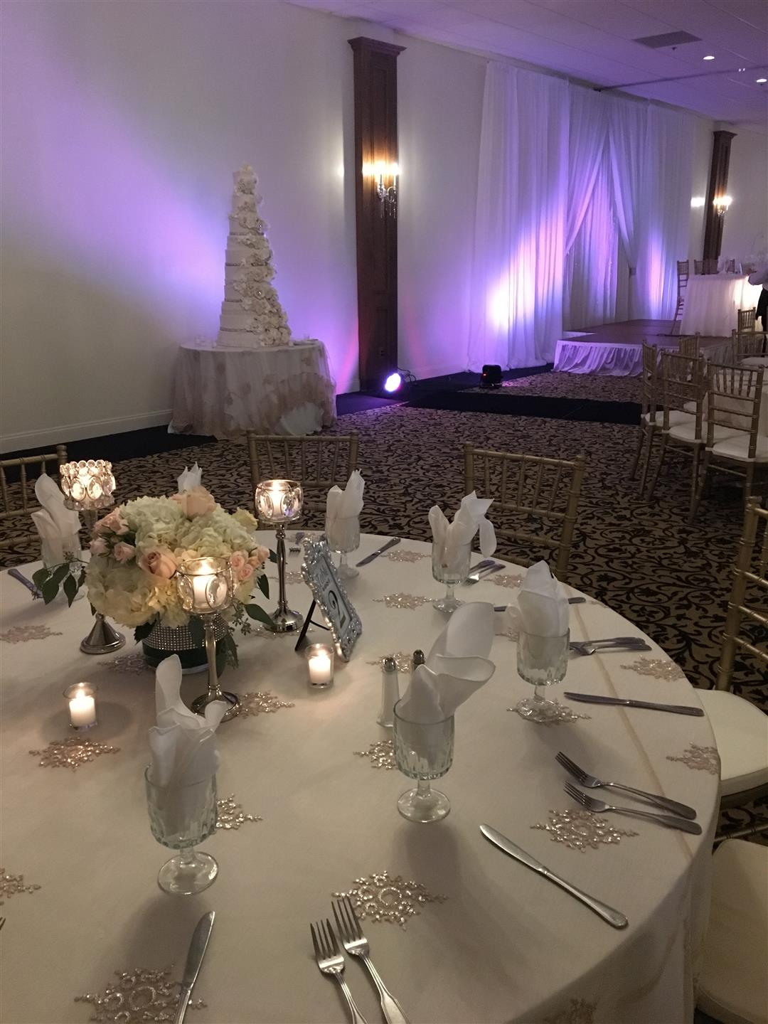 Wedding tables set up with glass wear and dish wear with wedding cake in the background