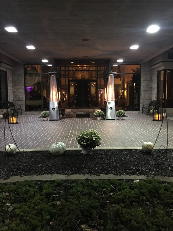 Outside entrance of venue with flowers and tall candles