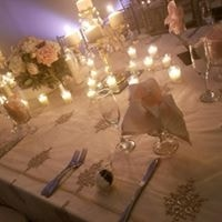 Wedding tables set up with glass wear and dish wear with candles with centerpiece in the middle