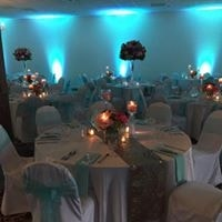 Wedding tables set up with glass wear and dish wear with tall floral centerpieces