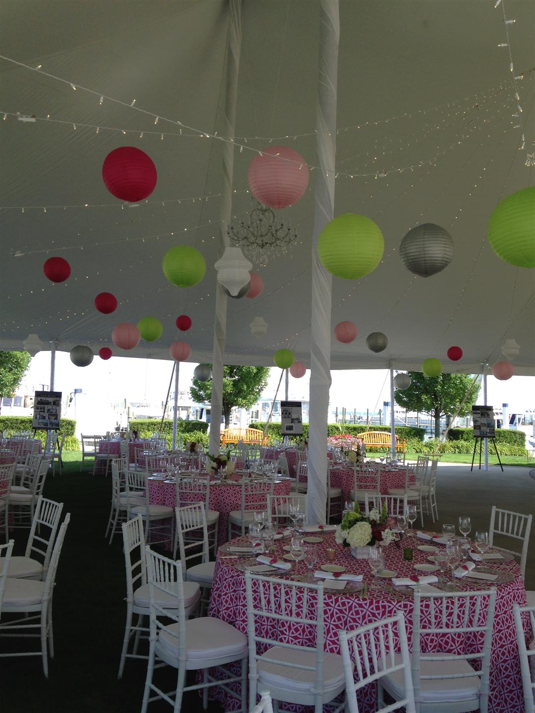 All wedding tables set up with white, link, and green lanterns hanging down