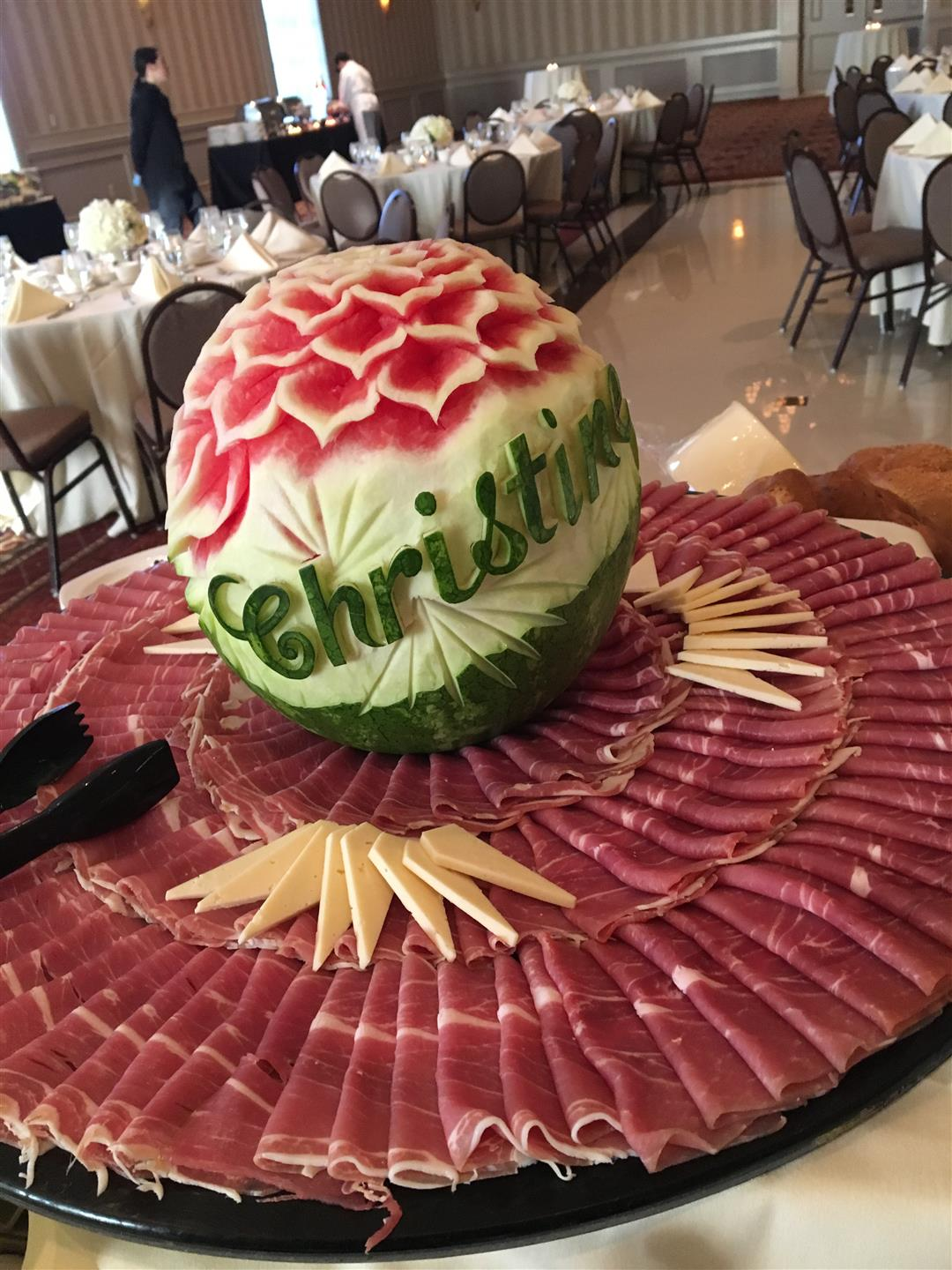 Carved watermelon on to of a meat and cheese platter