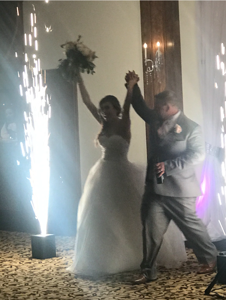 Wedding couple walking in to reception