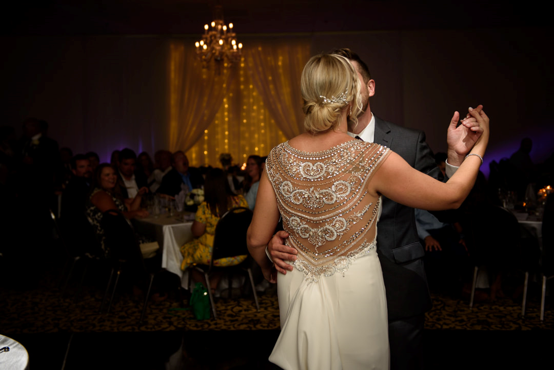 The bride and groom slow dancing.