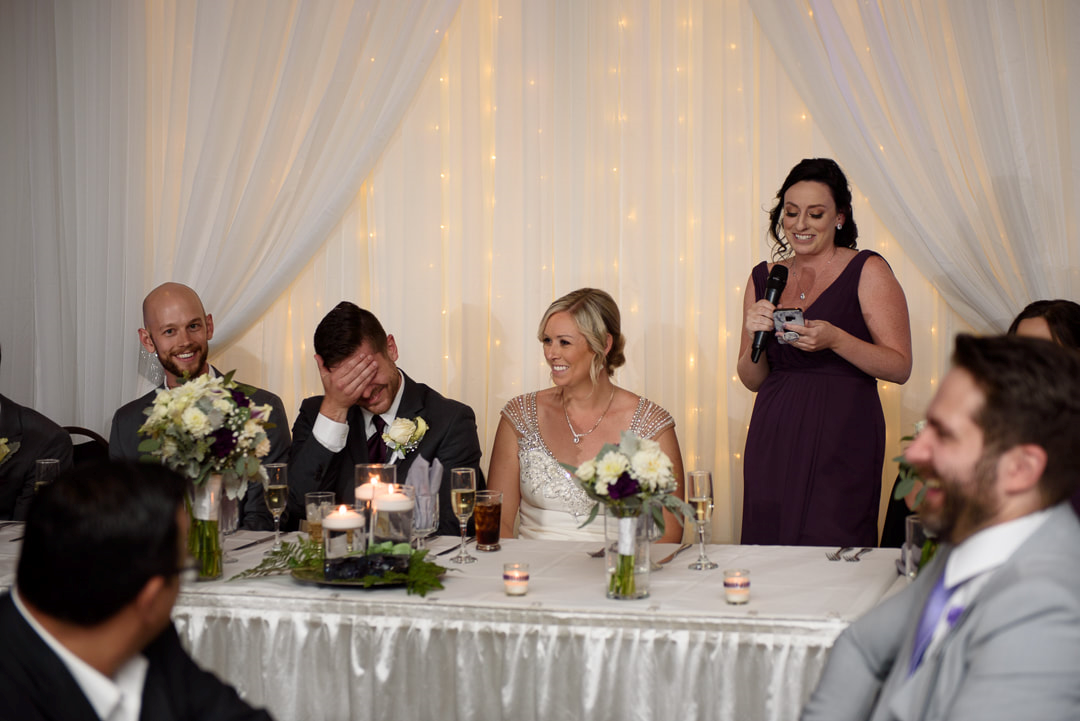 A bridesmaid giving a speech in front of the bride and groom